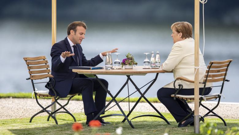 Emmanuel Macron stă de vorbă cu Angela Merkel la o terasă