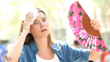 Sad woman fanning and sweating suffering a heat stroke