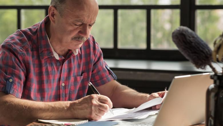 Senior hispanic man using calculator and calculate bills
