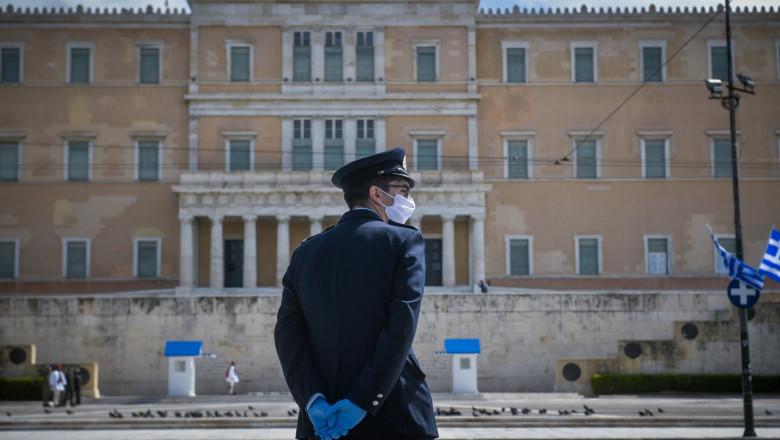 Polițist grec cu mască în fața parlamentului grec