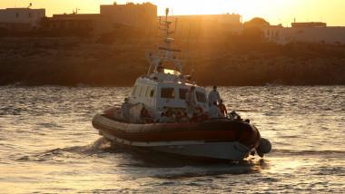 barcă transporta oameni la apus pe mare langa mal