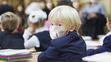 Elev mic purtand masca de protectie in clasa