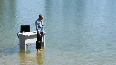 om de afaceri stand in apa cu picioarele goale si cu biroul in spate