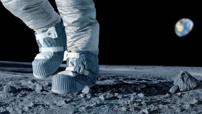Astronaut care pășește pe Lună. Pământul este vizibil în spate