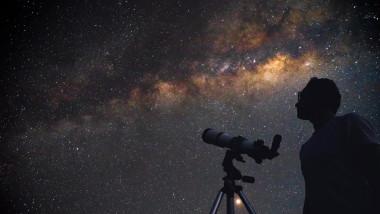 Astronom privește spre cer cu discul Căii Lactee vizibil