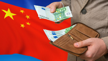 barbat scotand din portofel bancnote de euro pe fondul unui steag al chinei