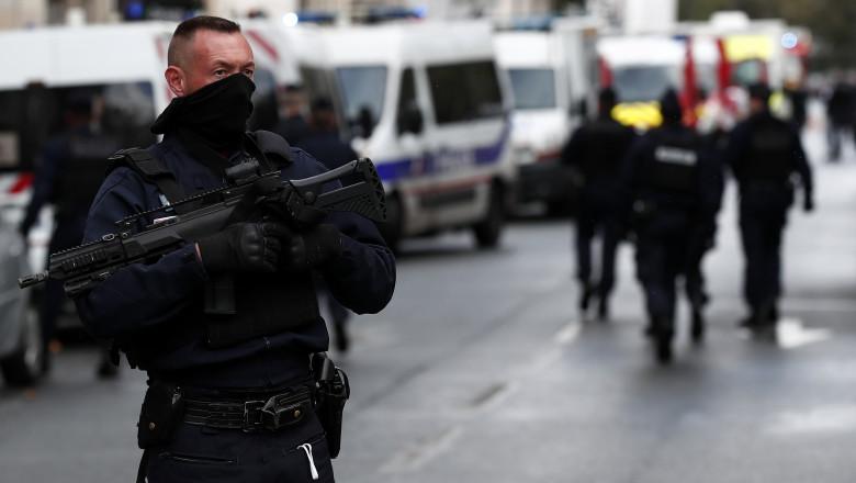 Un politist inarmat sta langa fostul sediul al revistei Charlie Hebdo, dupa atacul cu maceta de vineri