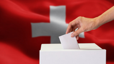 Close-up of human hand casting and inserting a vote and choosing and making a decision what he wants in polling box with Switzerland flag blended in background.