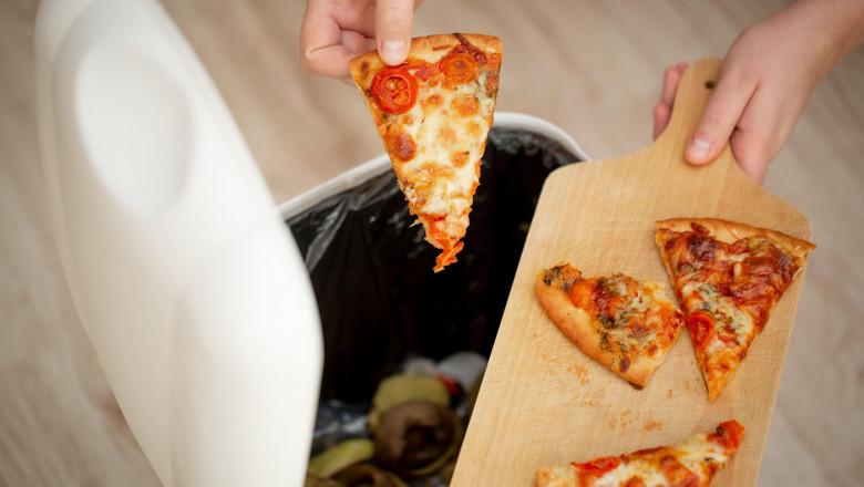 un om aruncă pizza la cosul de gunoi