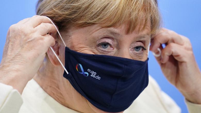 Angela Merkel își așază masca de protecție pe față.