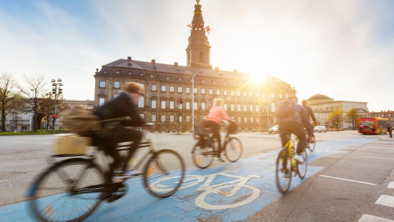 Oamenii preferă să meargă pe bicicletă prin Copenhaga. În fundal este Palatul Christiansborg