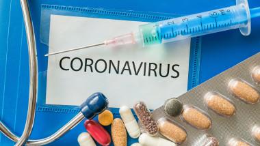 o seringa si medicamente langa o cartie pe care scrie coronavirus,