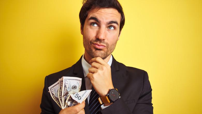 tanar om de afaceri sta pe ganduri cu bani in mana