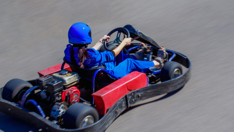 Karting on racing round in the open air. Woman behind the wheel of a kart. Girl rides on a kart with high speed.