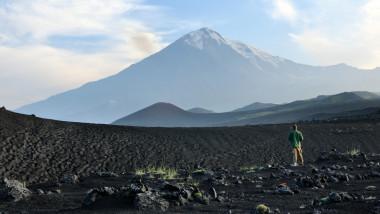 Un barbat sta in mijlocul unui camp, uitandu-se la vulcanul Tolbachik