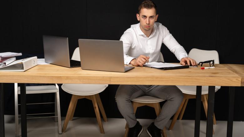 tanar serios munceste in fața a doua laptopuri