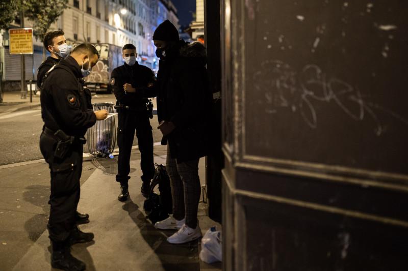 Poliţiştii francezi verifică o persoană pe străzile din Paris, după ora 21