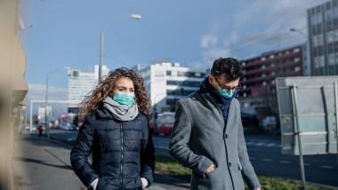 Doi tineri poartă masca de protecție pe stradă