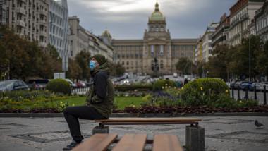 Un barbat cu masca se odihneste pe o banca, in centrul orasului Praga