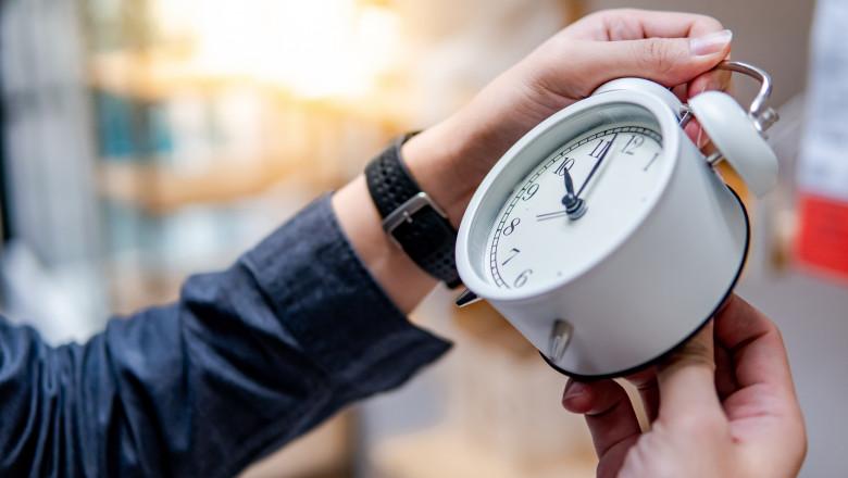 barbat care ajusteaza ceasul pentru a schimba ora