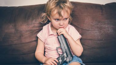 copil care se joaca cu arma parintilor
