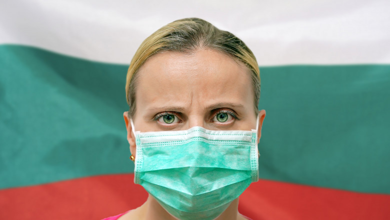 Face of a woman in a mask looking at the camera against the background of the Bulgaria flag. Influenza from coronavirus, prevention of pandemic virus infection. Virus in Bulgaria.