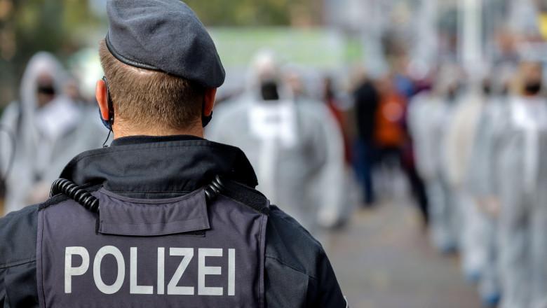restricţii coronavirus Europa, poliţist, demonstranţi anti restricţii în fundal