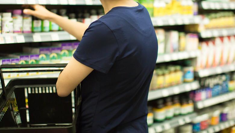 femeie alege suplimente alimentare de pe un raft din supermarket