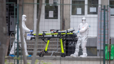 Bucharest, Romania - April 1, 2020: Romanian medical personnel wearing protective suits in the yard of a hospital closed for Covid-19 infection.
