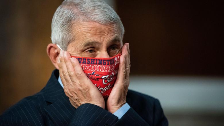 Imunologul american Anthony Fauci cu mâinile peste masca de protecţie