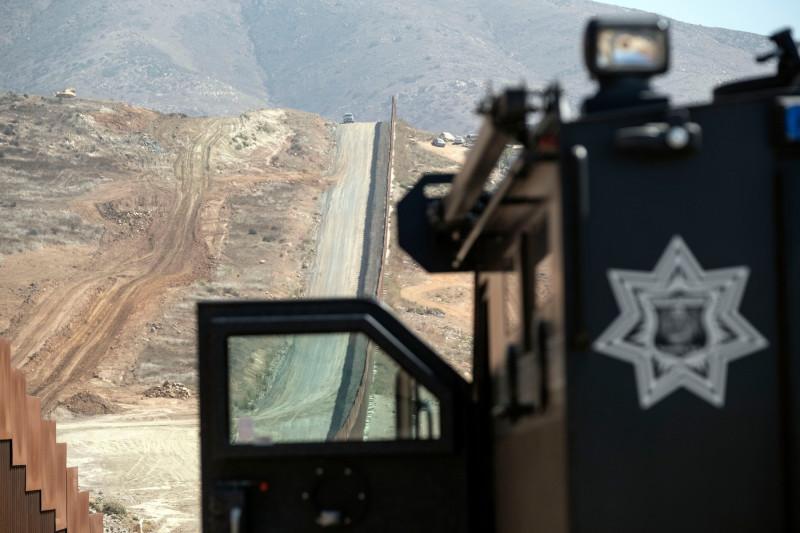 maşină de poliţie supraveghează zidul de la graniţa dintre SUA şi Mexic