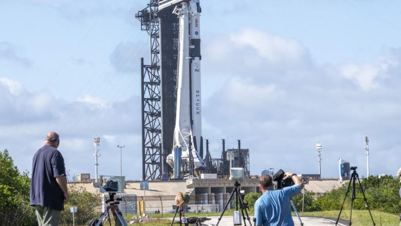 Un aligator începe să traverseze drumul în timp ce fotografii și operatorii își pregăteau echipamentele pentru a lua imagini de la pregătirea pentru lansare a rachetei Falcon 9 a SpaceX care va lansa sâmbătă capsula Crew Dragon cu patru astronauți la bord de la Cape Canaveral, Florida