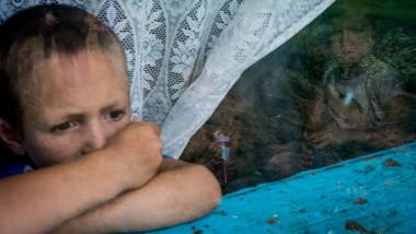 un copil sarac se uita pe fereastra