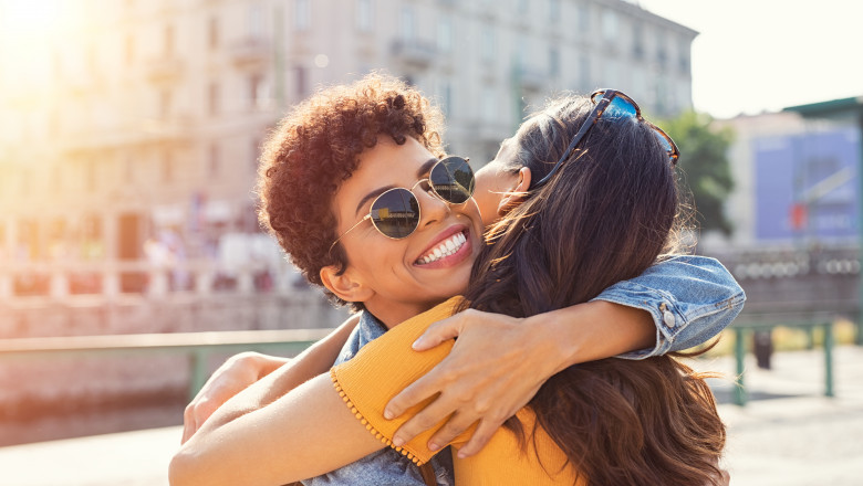 Two women hugging in town square