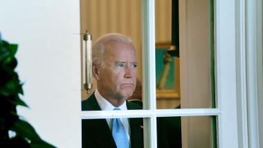 Joe Biden se uită printr-o fereastră la Casa Albă