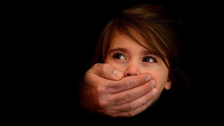 copil cu gura acoperita de o mana de barbat