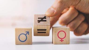 gender equality and discrimination concept - hand putting wooden blocks with symbols