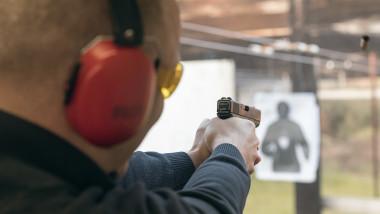 Bărbat trage cu pistolul într-un poligon închis
