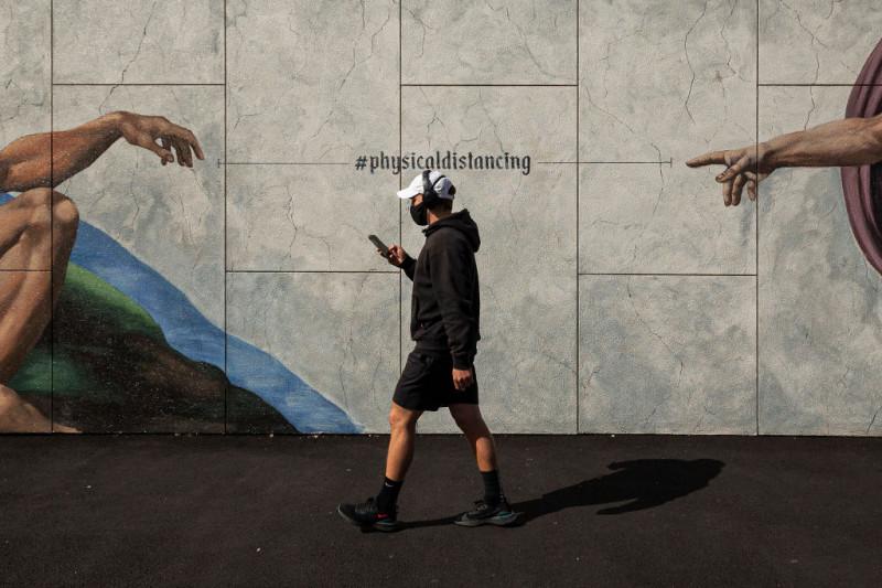 bărbat cu mască merge pe stradă pe lângă un grafitti despre distanţarea socială