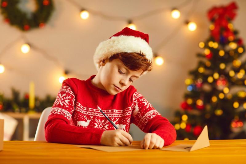 Băiat la masă scrie o scrisoare pentru Moş Crăciun