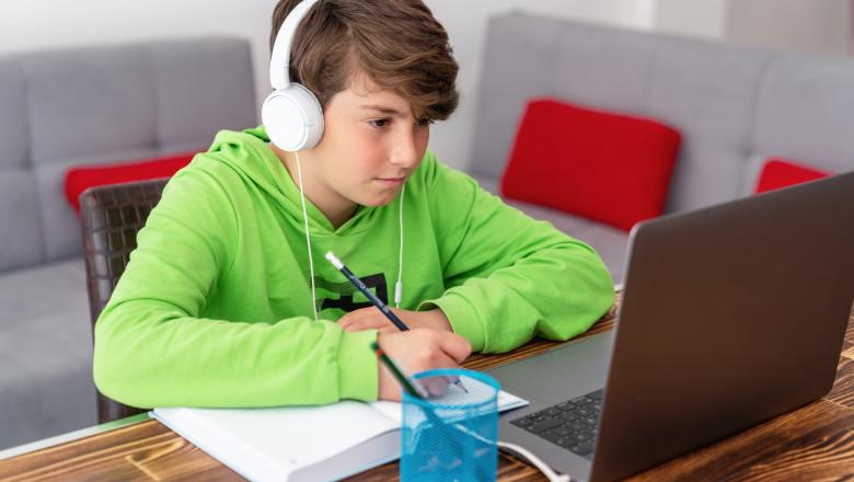 baiat in fata unui laptop face scoala online