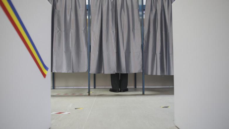un barbat voteaza in cabina de vot