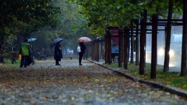 oameni cu umbrele asteapta in ploaie sa vina autobuzul