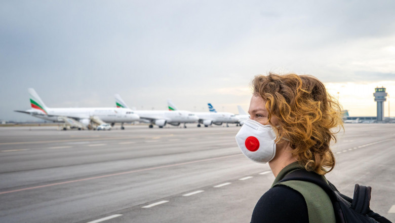 Woman with a mask on her mouth protects against the virus. Sadly looks at the aircraft parked at the airport. Canceled flights due to coronavirus