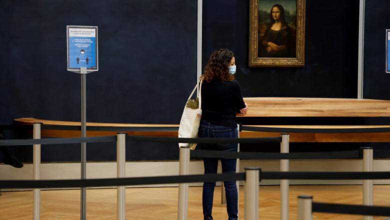 turistă cu mască la Luvru se uită la tabloul Mona Lisa