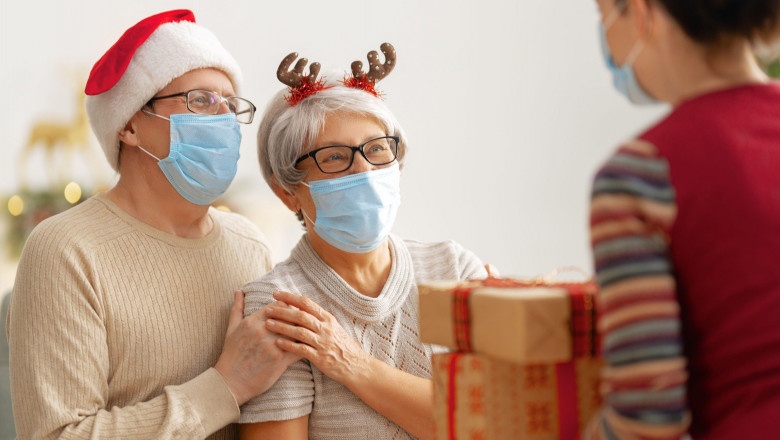 People with gifts wearing facemasks during coronavirus and flu outbreak on Christmas. Virus and illness protection, home quarantine. COVID-2019