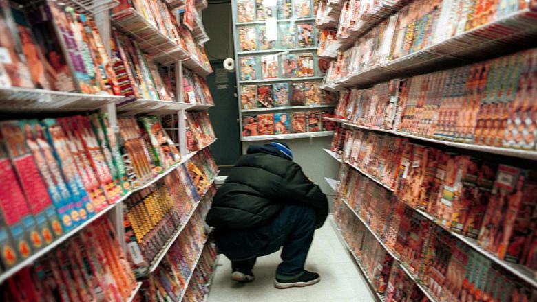 Magazin pentru adulţi în New York, client se uită la rafturile pline cu DVD-uri şi filme porno