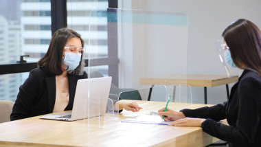 Manager from HR department wearing facial mask is interviewing new applicant who is handing her resume and profile through the partition for social distancing and new normal