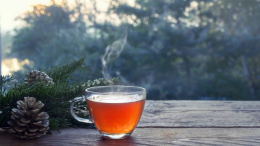 Cup with hot steaming tea on a rustic wooden garden table with Christmas decoration on a winter day, health concept against cold and flu, copy space,