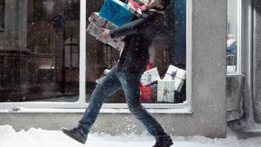 Man carrying Christmas gifts in snow